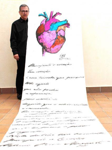 1 Miguel Elías junto a su Rollo caligrafiado con el poema Pasaporte el Corazón, de A. P. Alencart