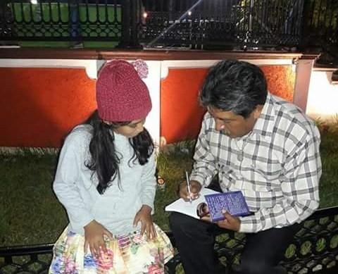 5 Tun Ku dedicando su libro a un niño
