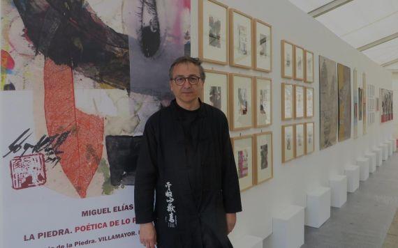 1 Miguel Elías con el cartel de su exposición y parte de la muestra (foto de Jacqueline Alencar)